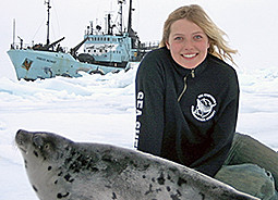 A crewmember enjoys a peaceful moment with a baby harp seal (the Sea Shepherd flagship Farley Mowat in the background).